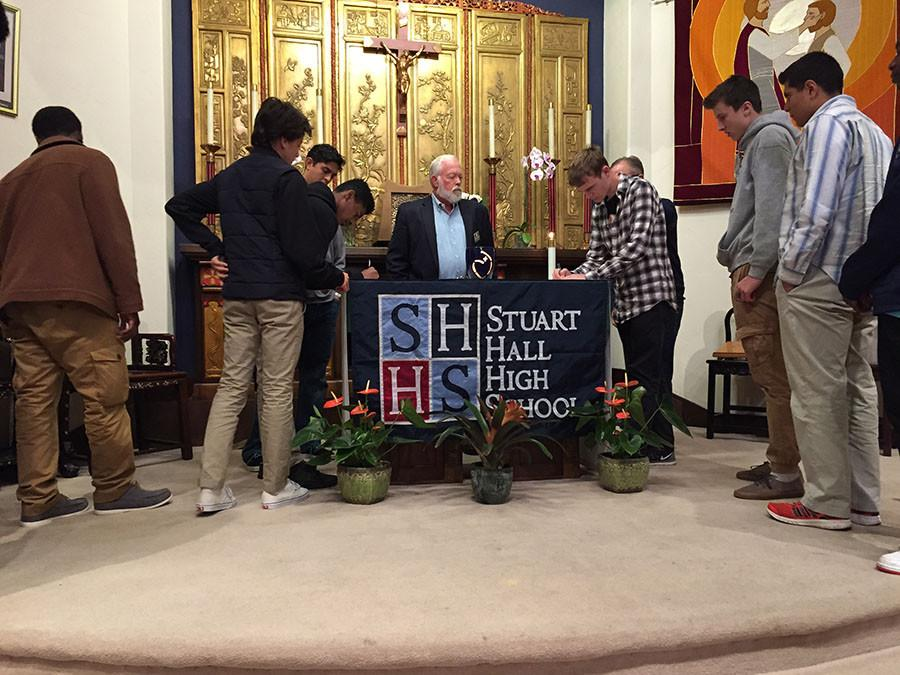 Mr. Marquette oversees the signing of the Honor Coed at last Friday's chapel.