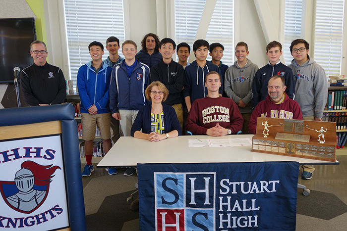 Students and family join Zack as he signs his letter of intent to attend Boston College.