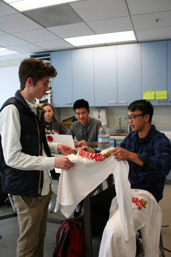 Michael Liu '18 sells a shirt to Dylan Kelly '17 at the end of art class in Siboni. Liu founded his shirt company with a few of his friends and has been selling shirts at school for the majority of the second semester.