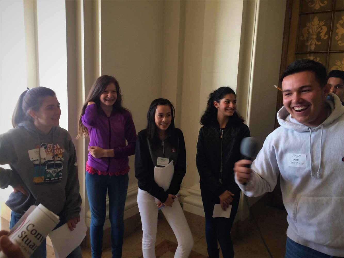 Angel Padilla '18 directs a group of students to sing a song with the for