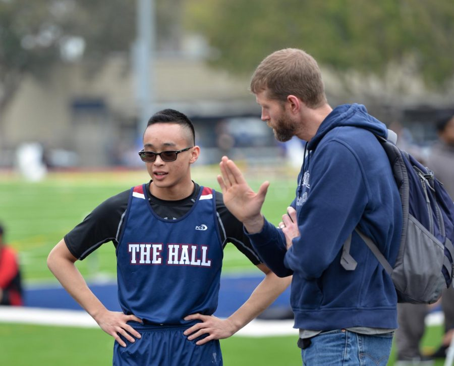 Head Coach Michael Buckley intructs sprinter and jumper Nick Ong '19 during the King's Academy Invitational track and field meet earlier this month. Ong has emerged as one of The Hall's top athletes in his third year on the team and looks poised to be a contributor this year and next.