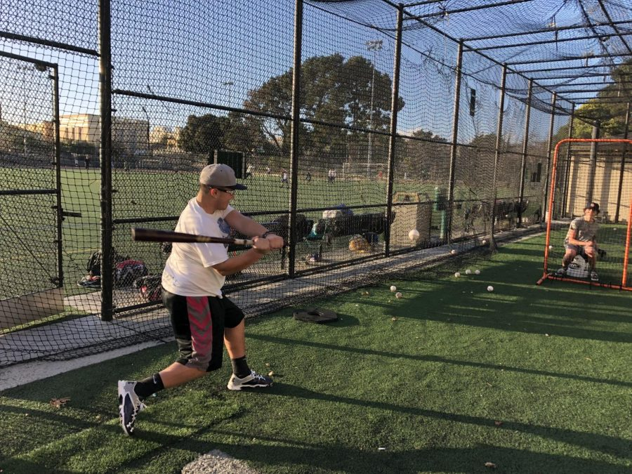Angel Padilla '18 takes batting practice at Kimbell field after school. The baseball team has been forced to find alternative ways to practice to due to the rains which have closed grass fields through much of March.
