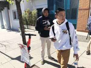 Senior Cole Slater and junior Trieu Tran wait for the school shuttle next to a Jump scooter parked in front of the Pine/Octavia campus. Electric scooter-sharing systems like Jump, Skip, Spin and Lime brought thousands of new scooter units to San Francisco after securing city permits in 2019, but the rise in scooters is correlated with a rise in injuries.