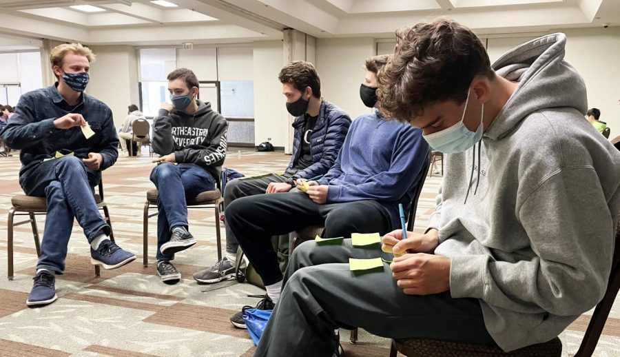 Senior Chase Mack writes down highs and lows from each year of high school on Post-its prior to sticking them to a wall during a Senior Retreat activity. Seniors separated into their advisories and took turns walking around the venue to put up and read each other's memories.