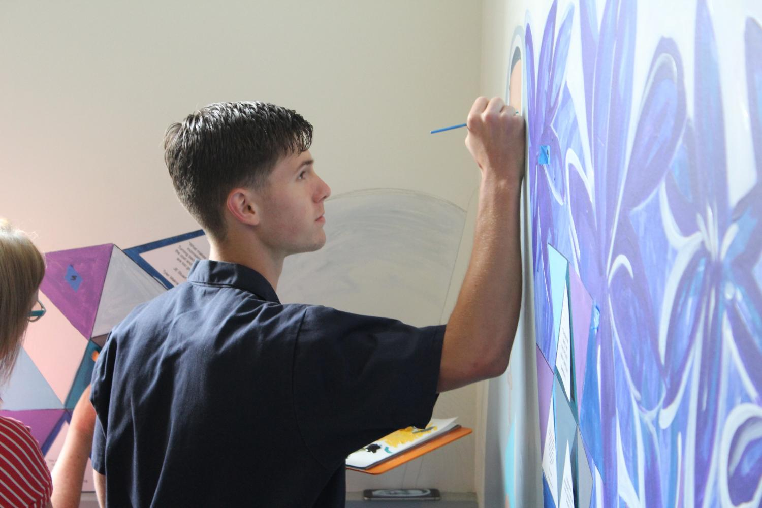 Edward Emery '17 works on the mural at the Pine & Octavia campus. Emery assisted Artist-in-Residence Patter Hellstrom in finishing the mural that every junior has contributed to.