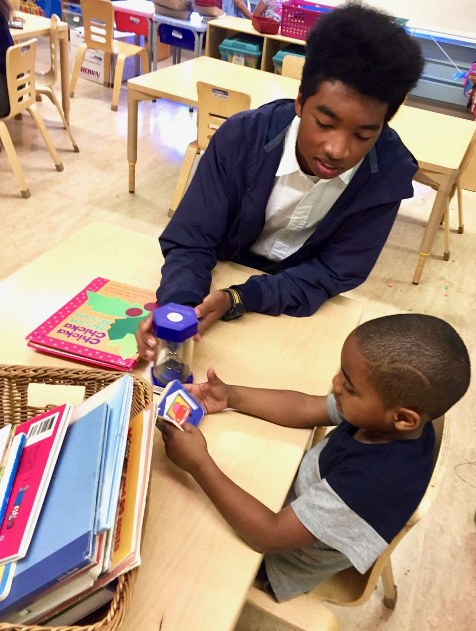 Phoenix Aquino-Thomas '18 plays with a student during his lunch break as a part of the service requirement for his theology class. Students engage in service at sites all around the city.