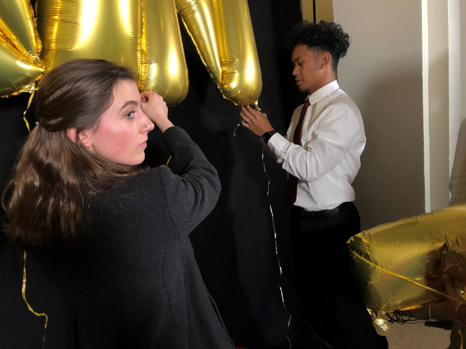 Seniors Wellsley Cohen and Skyler Dela Cruz decorate the Flood Mansion's Gallery for Winter Formal on Jan. 25. The gambling-themed annual dance featured snacks, drinks, card games and a dance floor in the Reception Room.