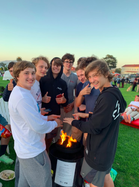 Knights football players gather around fire at Off the Grid. Players left practice at Kesar Stadium in Golden Gate Park early to attend the event.