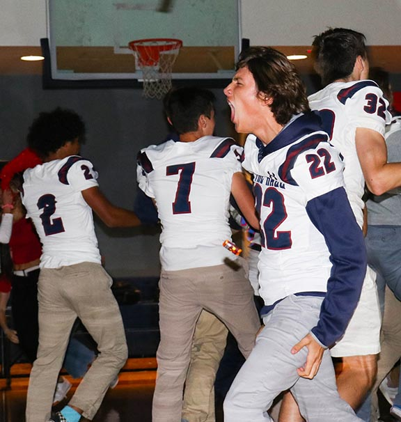 Junior Owen O'Dell runs out with the football team during the Pep Rally on Sept. 13. The event started Spirit Week, which will feature two games, a dance and special dress days.