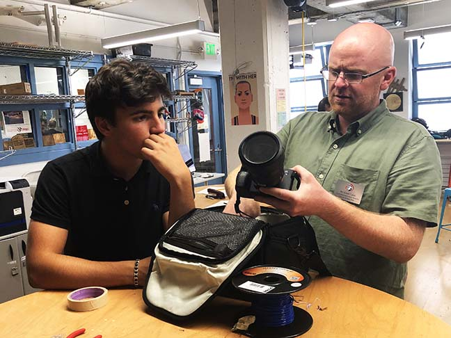Liam Carey, Computer Science and Digital Design instructor, shows junior Eon Kounalakis a Sony camera from the Digital Media Library. In preparation for the school year, the Department of Tech and Innovation set up AssetTiger, a program that facilitates keeping track of the equipment and sends notification emails to users.