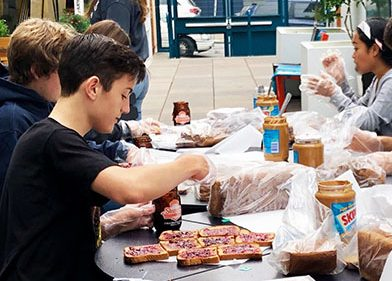Freshman Vlad Korostoshevskiy helps prepare bag lunches for the homeless on Sept. 15. Although Students in Action organized the first One Less Hungry event of the year, most participants were not members of the club.