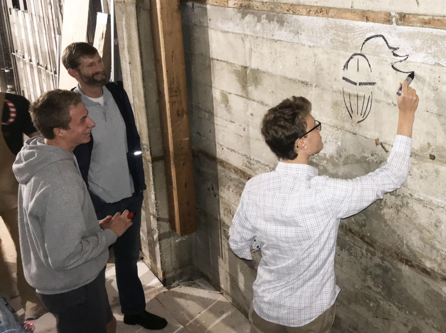 Senior Maxi Tellini draws the Stuart Hall Knight on the concrete of the Columbus Room before the construction crew begins putting up drywall this week. Although the room will be open to the students mid-winter, the kitchen will not be completed until February.
