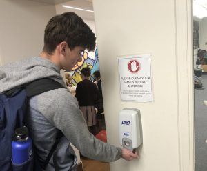 Senior Collin Ritchie uses hand sanitizer outside the Spark Studio before lunch. SAGE, the school's catering service provider, increased hand sanitizer availability in the cafeteria.