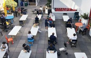 Students eat lunch in the Courtyard of the Pine/Octavia campus. The 15 long tables accommodated two people at a time, and 11 round tables accommodated one person.