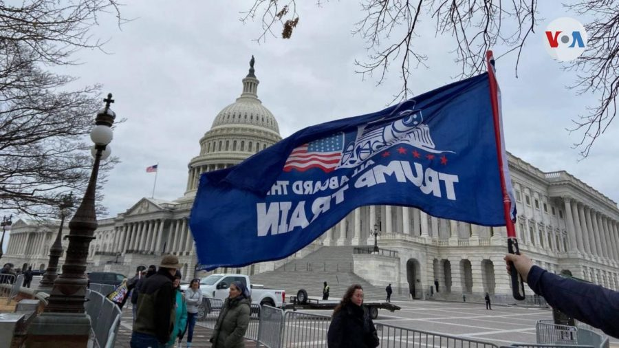 A protester holds a pro-Trump flag across from the U.S. Capitol Building prior to the beginning of the riot on Jan. 6, 2021. Pro-Trump extremists, some of whom were armed, breached the building, resulting in 52 arrests and at least 56 police officer injuries.