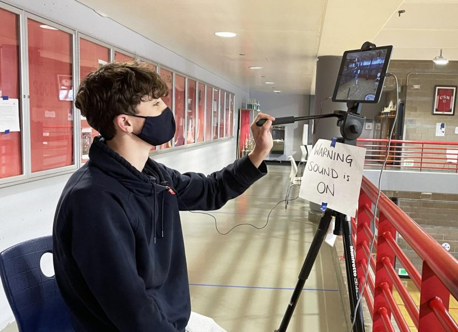 Junior Isaiah Ryan tests an iPad camera and microphone prior to a Knights basketball frosh-soph game against Urban High School in the Herbert Center on May 7, 2021. The Zoom livestream included real-time commentary.