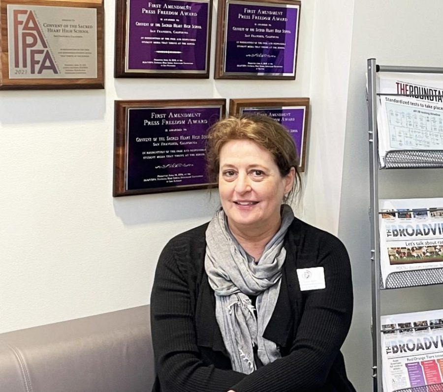Tracy Sena, Scholastic Journalism & Media Director, sits in front of the Publications Lab with seven years of First Amendment Press Freedom Awards behind her. Sena facilitated a journalism program in which student work has been nationally recognized for its excellence.